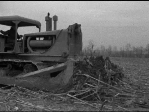 field w/ vegetation stalks on ground tu ms bulldozer moving into frame right tracking bulldozer w/ 'allischalmers' label pushing dirt senior male... - levittown pennsylvania stock videos and b-roll footage