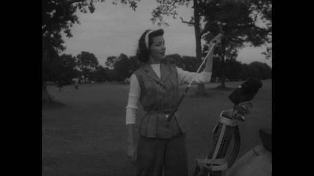 vídeos de stock, filmes e b-roll de ms field with trees in background as golf cart drives into frame and louise a young model dressed in plus fours gets out of cart selects a golf club... - golf cart