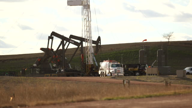 fields and drilling rigs in watford city, north dakota, us, on november 3 wide shot of grass blowing in the wind, wide shot of an oil tanker driving... - cricket stump stock videos & royalty-free footage