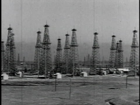 vídeos de stock, filmes e b-roll de 1929 montage fields filled with oil derricks / united states - 1920 1929