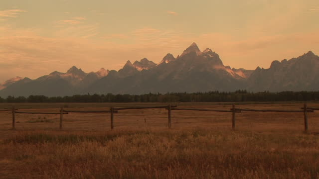 zi, ms, fields with mountain range in background, grand teton national park, wyoming, usa - grand teton national park stock videos & royalty-free footage