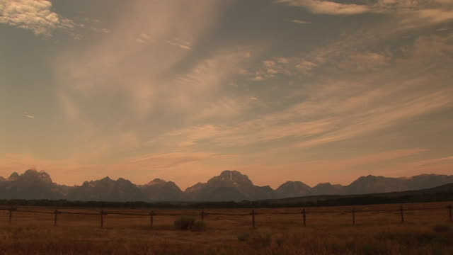 WS, PAN, Fields with mountain range in background, Grand Teton National Park, Wyoming, USA