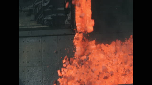 cu fiery hot coke pours into moving rail cars breaking into chunks as it hits - eisenerz stock-videos und b-roll-filmmaterial