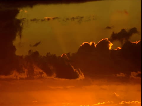 fiery orange sky with sun glowing behind dark clouds no horizon visible - orange colour stock videos & royalty-free footage