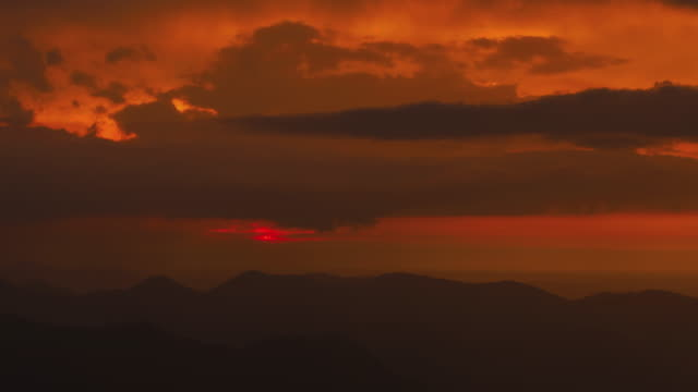 stockvideo's en b-roll-footage met t/l fiery sunset timelapse in the bavarian alps as seen from the summit of mount wallberg on a stormy and rainy day - bavarian alps