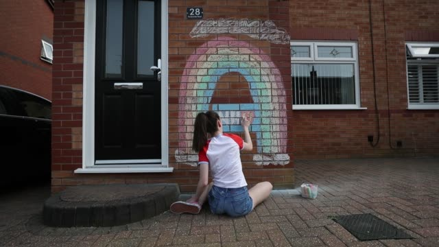 fifteen-year old maisy byrne draws a rainbow and and nhs logo onto the wall of her home in liverpool in support of the nhs workers. - rainbow stock videos & royalty-free footage