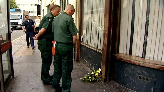 relatives hold ceremony members of ambulance service looking at flowers on ground outside kings cross station and edgware road and row of red roses... - memorial plaque stock videos and b-roll footage