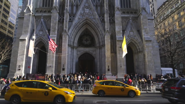 fifth avenue traffic goes through at front of many worshipers for christmas day mass at st. patrick's cathedral during the christmas holidays season at new york city ny usa on dec. 25 2019. - yellow taxi stock videos & royalty-free footage