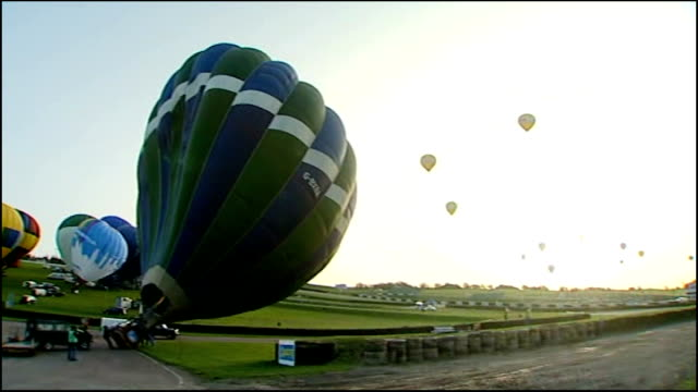 fifty balloonists cross english channel to set new world record england kent lydden hill race circuit ext wide shot hot air balloons being inflated... - world record stock videos & royalty-free footage