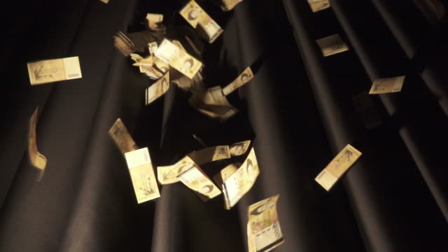 Fifty Thousand Won paper bills falling from the sky and black back drop (South Korean Currency)