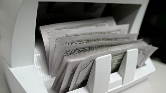 SLO MO LD Fifty US dollar banknotes coming out of the money counter and stacking up