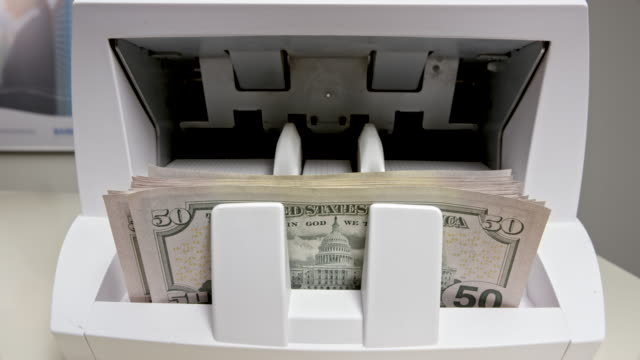 LD Fifty US dollar bills coming out of the money counting machine and stacking up
