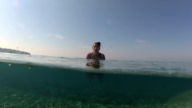 vídeos de stock, filmes e b-roll de subaquático, fiftyfifty, sob/sobre: mulher adorável nadando no oceano - nível da superfície