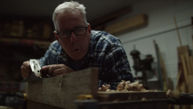 a fifty-something caucasian male woodworker in a plaid shirt uses a no.5 vintage hand plane along the edge of a red oak board creating wood shavings in a workshop - man made stock videos and b-roll footage