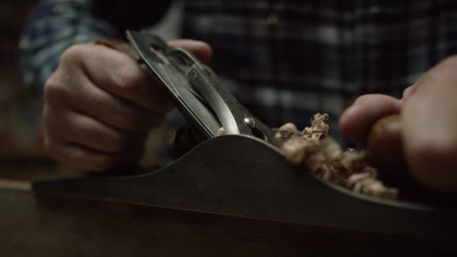 A Fifty-Something Caucasian Male Woodworker in a Plaid Shirt Uses a No.5 Vintage Hand Plane Along the Edge of a Red Oak Board Creating Wood Shavings. The Camera Tilts Up to Reveal the Woodworker.