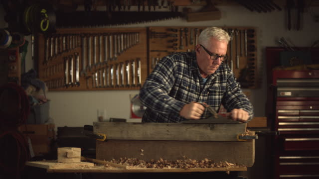 a fifty-something caucasian male woodworker in a plaid shirt uses a no.5 vintage hand plane along the edge of a red oak board creating wood shavings in a workshop - hobbies stock videos & royalty-free footage