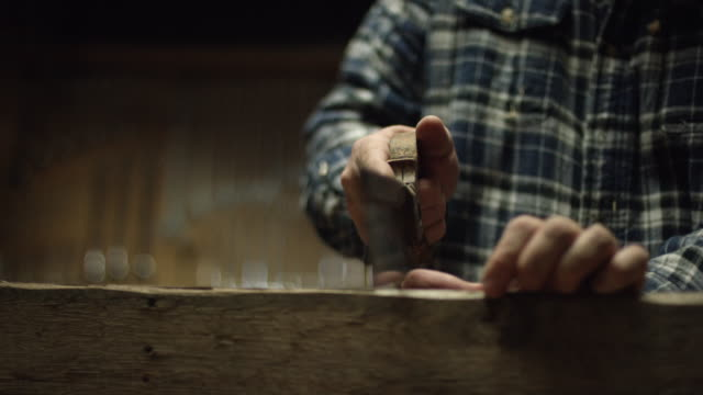 a fifty-something male woodworker in a plaid shirt uses an antique hand saw to saw a red oak board in a workshop - hand saw stock videos and b-roll footage