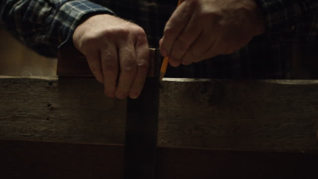 A Fifty-Something Male Woodworker Uses an Antique Square and a Pencil to Mark Measurements on a Red Oak Board. Then the Camera Tilts Up to Reveal the Woodworker's Face.