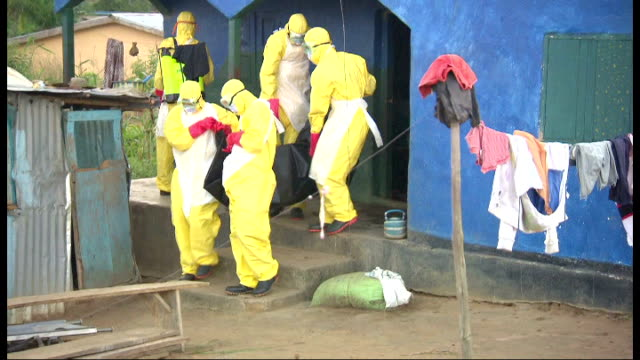 fight against ebola continues one year on from first case t21101401 freetown ext workers in protective full body suits carrying ebola victim from... - dead person stock videos & royalty-free footage