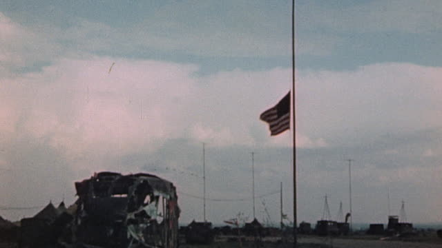 p47 fighter airplanes flying in v formation over a steel hangar over an american flag flying at half mast and four p47s circling for landing - ve day stock-videos und b-roll-filmmaterial