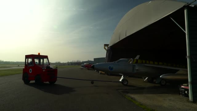 a fighter jet being towed from a hangar - airfield stock videos & royalty-free footage
