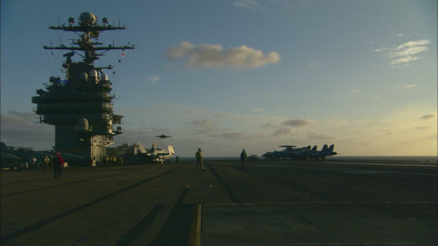 MS, PAN, fighter jet landing on aircraft carrier deck at sunset, ground crew watching