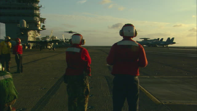 MS, PAN, fighter jet landing on aircraft carrier deck, two ground crew watching