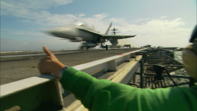 vídeos de stock e filmes b-roll de ms, fighter jet taking off aircraft carrier deck - avião de combate