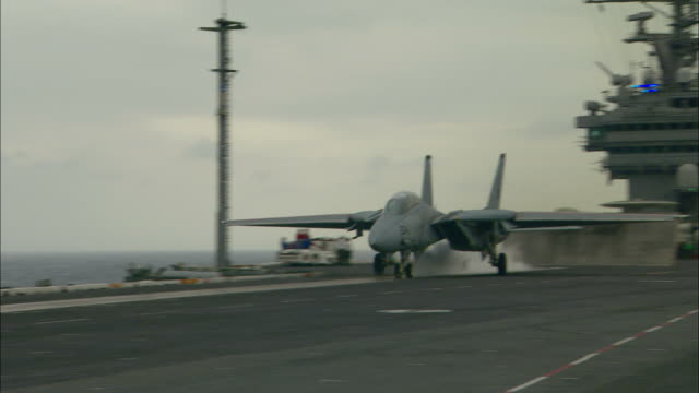 ms, pan, fighter jet taking off aircraft carrier - aereo militare video stock e b–roll