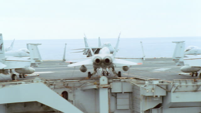 vidéos et rushes de fighter jets and crew members line the decks of an aircraft carrier. - flotter sur l'eau