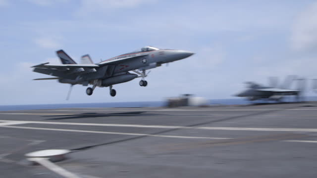 fighter jet's tailhook catches arresting wire on aircraft carrier for landing, medium shot - aircraft carrier stock videos & royalty-free footage