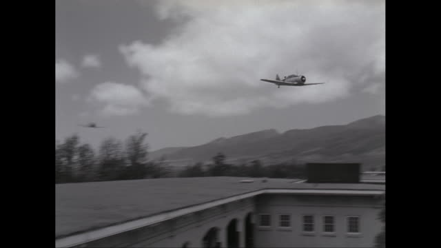 ws ts fighter plane flying over military building / united states - pearl harbor stock videos and b-roll footage