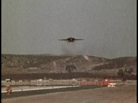1979 montage fighter plane lands in sight of air traffic control tower/ united states - air traffic control点の映像素材/bロール
