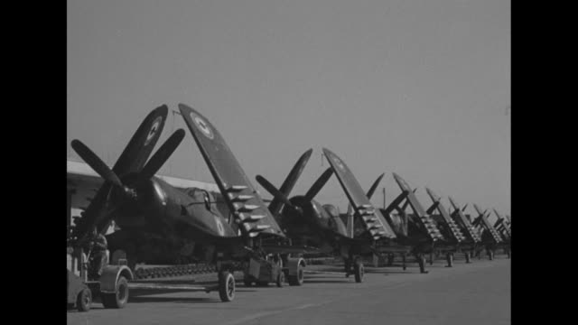 fighter planes with japanese markings, their wings tilted up, are towed by tractors along roadway; these are on loan to japan during the korean war /... - anchored stock videos & royalty-free footage