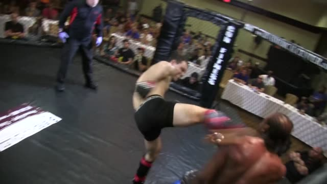 vídeos y material grabado en eventos de stock de / fighter takes out opponent with a kick to the head who goes down immediately referee stops fight - oficial deportivo