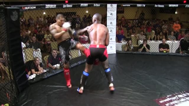 vídeos y material grabado en eventos de stock de / fighter trying to kick his opponent is backed against the ropes falls to the mat after being punched in the face referee stops the fight - oficial deportivo