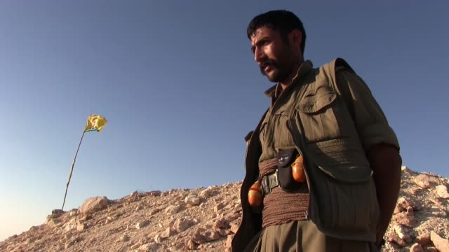 A PKK fighter with a flag fluttering in background bearing the figure of Abdullah Ocalan founding member of militant organization of Kurdistan...