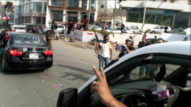 fighters celebrate death of gaddafi libya benghazi new libyan flag flying from car as car speeding along ext various of celebrations in streets and... - muammar gaddafi stock videos & royalty-free footage