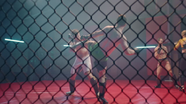 mma fighters throwing punches in octagon. hitting the net. female fighters in background - octagon stock videos & royalty-free footage