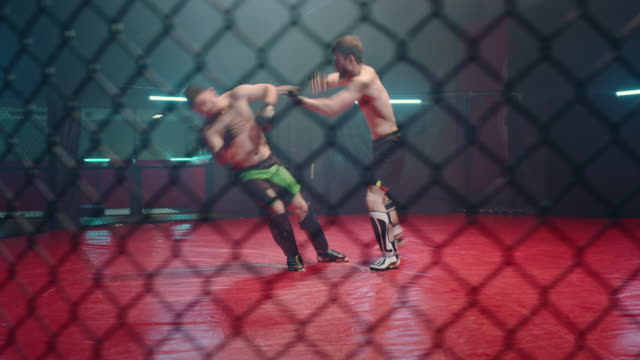 mma fighters throwing punches in octagon. knockout - boxing stock videos & royalty-free footage