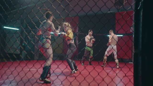 mma fighters training in octagon. two fights. women hitting the net in foregroumd - octagon stock videos & royalty-free footage