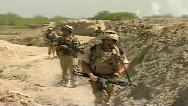 fighting continues against taliban / eyewitness account of ambush; smoke rising in sky general views of royal marines towards - 英国海兵隊点の映像素材/bロール