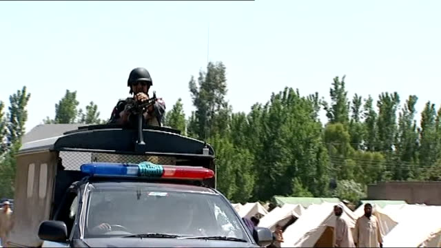 Fighting continues against Taliban in Swat Valley refugees flee area Man holding piece of bread and empty bowl Soldier manning weapon on top of truck...