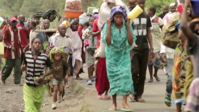 fighting continues / evidence of rwandan backing of rebel forces; democratic republic of congo: ext congolese refugees towards with belongings... - democratic republic of the congo stock videos & royalty-free footage
