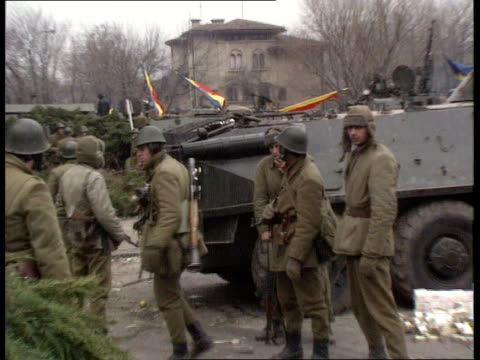 vídeos y material grabado en eventos de stock de fighting goes on; romania: bucharest: tv centre seq armed troops with defensive ring of tanks and apcs surrounding tv centre night seq flames in... - rumania