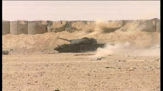 Fighting with Taliban rebels continues Explosions around tank in desert Side view of British soldier firing rifle Side view of two British troops...
