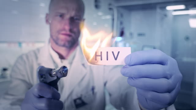 vídeos de stock e filmes b-roll de fighting with viruses. lab worker setting on fire word 'hiv' - hiv