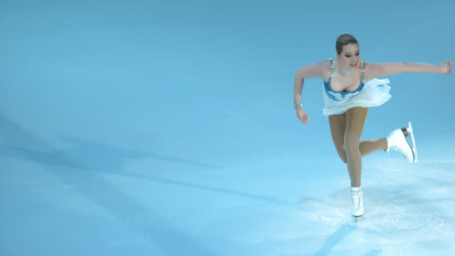 slo mo pan figure skater in a sit spin variation - figure skating stock videos and b-roll footage