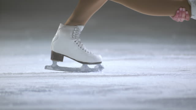 slo mo figure skater performing a basic sit spin - ice skater stock videos and b-roll footage