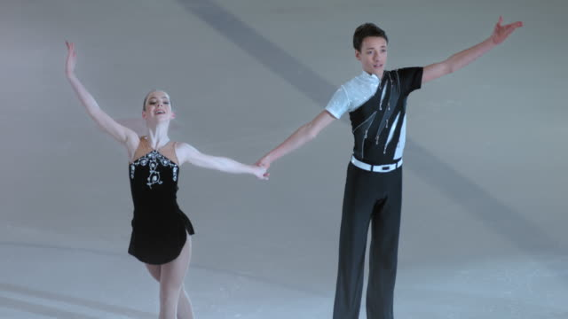 slo mo figure skating pair bowing to the audience - ice skating stock videos and b-roll footage